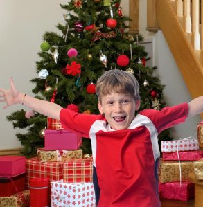 Stevie jumping in front of his family's Christmas tree, which is surrounded by presents.