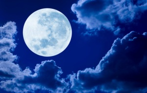 A picture of a full moon, up in the sky, surrounded by clouds.