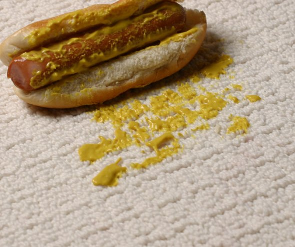 Picture of hot dog that has just been dropped on white, Downs carpet. Fortunately, the mustard mess won't stain Downs.