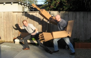Two adult men; one wearing cardboard robot arms is chasing the other.
